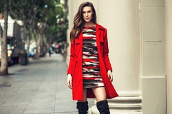 Fashionable brunette woman in red coat and nice dress, sunglasses walking in the street. Fashion autumn photo