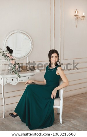 Fashionable brunette woman with stylish hairstyle in stylish evening dress and in trendy shoes sits at the dressing table #1383215588