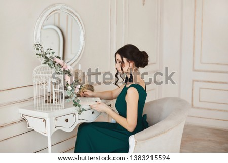 Fashionable brunette woman with stylish hairstyle in stylish evening dress and in trendy shoes sits at the dressing table