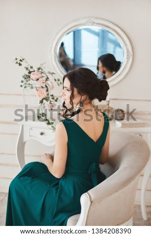 Fashionable brunette woman with stylish hairstyle in stylish evening dress and in trendy shoes sits at the dressing table #1384208390