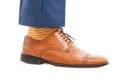 Fashionable business man foot in closeup wearing formal suit and colorful socks on white background