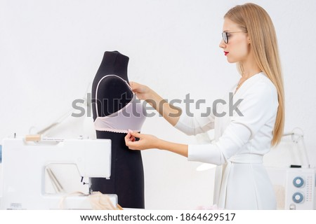 Fashionable business tailor underwear, seamstress woman tries on bra on mannequin. Stock fotó ©