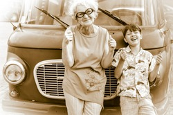Fashionable, cheerful grandmother with her grandchild are fooling around a retro car imitating driving. Summer family vacation and travel. Retro style. Sepia