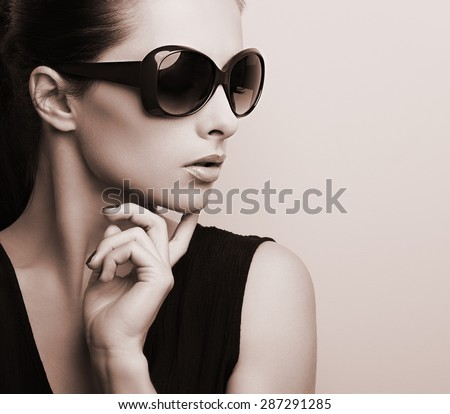 Fashionable chic female model profile in fashion sunglasses posing. Black and white color toned portrait