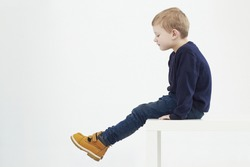 Fashionable child in yellow boots. fashion kids.children.little boy sitting on a table
