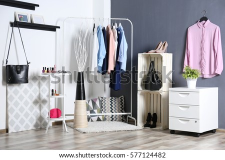 Fashionable clothes hanging on rack at modern dressing room #577124482