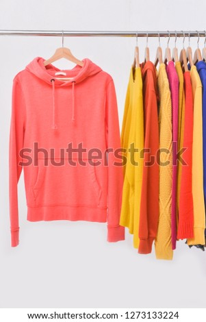 Fashionable clothing on hangers in shop. sports warm jacket, hoodie ,sweater shirts  are hanging on Clothes Hanger, clothes hanger with sports warm jacket.