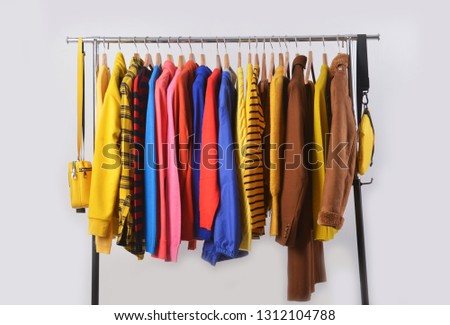 Fashionable clothing on hangers in shop. sports warm jacket, sweater stripy shirts  are hanging on Clothes Hanger, clothes hanger with sports warm jacket.