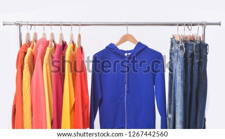 Fashionable clothing on hangers sports warm jacket, Hoodie sweater stripy shirts  ,blue jeans are hanging on Clothes