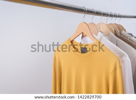 Fashionable clothing on hangers. sports warm jacket, sweater ,suit are hanging on Clothes Hanger,