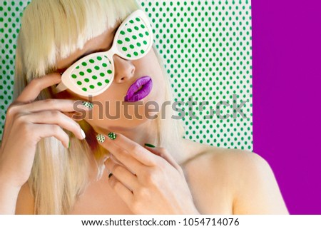 Fashionable coloring hair on light hair with bangs and glasses on the eyes.Nail design and makeup with green dots on model on background with dots. #1054714076