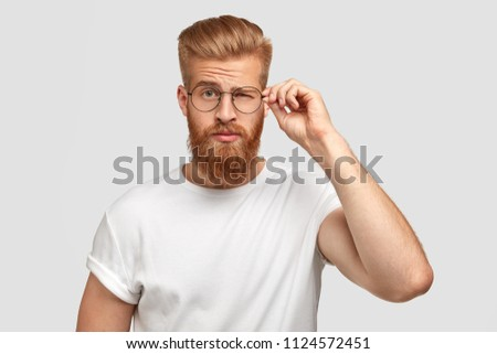 Fashionable cool male youngster with thick beard, blinks with eye, wears round spectacles, dressed in casual white t shirt, isolated over white background. People, style and emotions concept