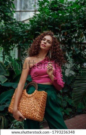 Fashionable curly woman wearing pink asymmetric ruffled top, green trousers, holding straw wicker top handle bag, posing in tropical garden. Summer fashion, lifestyle, beauty conception Zdjęcia stock ©