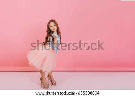 Fashionable cute young girl with long brunette hair, in stylish tulle skirt wearing big mother`s shoes, sending kiss to camera isolated on pink background. Having fun of joyful kid. Place for text #655308004
