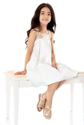 Fashionable dark-haired little girl in a beautiful beige dress sitting on white couch with his feet dangling. -Isolated on white background