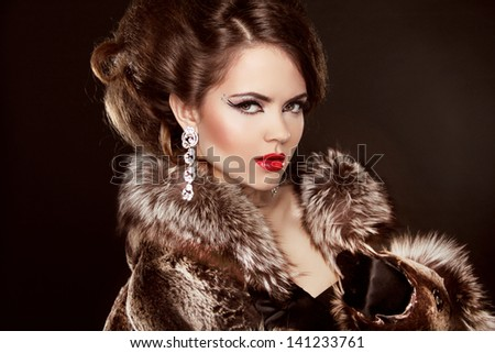 Fashionable elegant Girl in Luxury Fur Coat. Red Lips. Hairstyle. Jewelry and Fashion.