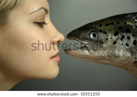 fashionable elegant girl with big fish on dark background