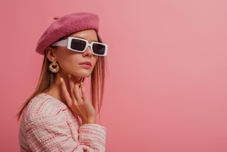 Fashionable, elegant woman wearing classic beret, stylish rectangle white frame sunglasses, trendy pearl earrings, posing on pink background. Copy, empty space for text