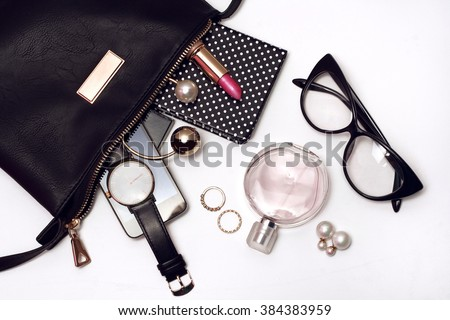 Fashionable female accessories watch glasses lipstick perfume and black bag. Overhead of essentials for modern young woman.