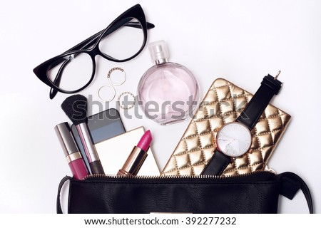 Fashionable female accessories watch glasses lipstick perfume and black purse. Overhead of essentials for modern young woman.