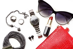 Fashionable female accessories watch sunglasses lipstick and red purse. Overhead of essentials for modern young woman.