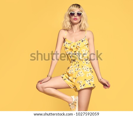 Fashionable female Blond model, Trendy Sunglasses. Stylish Glamour Summer Yellow Outfit. Young Beautiful European girl Posing in Studio. Gorgeous woman