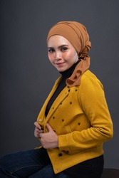 Fashionable female model in dark blue jeans, long sleeves yellow leather jacket with hijab isolated on grey background. Stylish Muslim hijab fashion lifestyle portraiture concept.