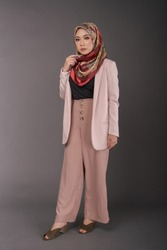 Fashionable female model wearing wide-leg trousers and pink blazer with colorful hijab isolated on grey background. Stylish Muslim hijab fashion lifestyle portraiture concept.
