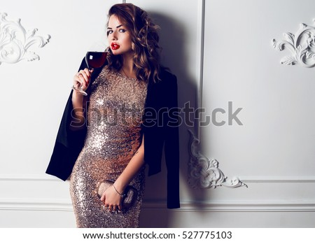 Fashionable  flash portrait of sexy brunette woman  dressed up for celebration new year or birthday party.  Seductive girl with trendy   shining purse drinking wine.