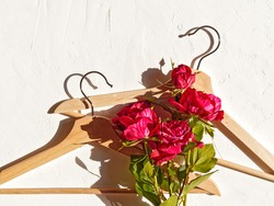 Fashionable flower arrangement. Layout of red rose flowers and wooden coat hanger. Template for sales of clothing, accessories, underwear. Flat lay. Top view. Copy space.