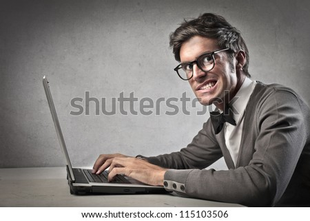 Fashionable forcibly smiling while using a laptop computer