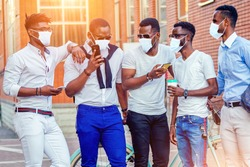 fashionable friends at a meeting. a group of five handsome African American men well-dressed in medical mask businessmen having fun and communicating in the summer in the park