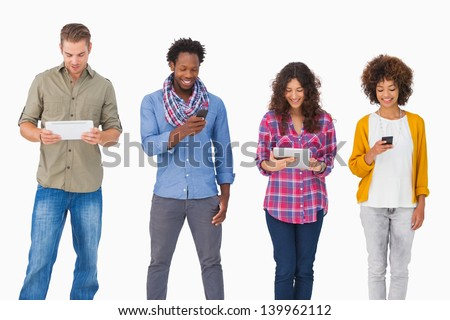 Fashionable friends standing in a row using media devices on white background
