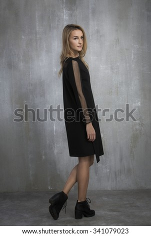 fashionable girl in black dress standing on a gray background, textured wall. #341079023