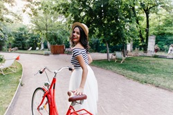 Fashionable girl in long white skirt having fun in summer weekend. Outdoor portrait of amazing brunette lady with bicycle looking over shoulder.