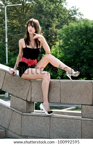 fashionable girl in park. Sits on  stone handrail