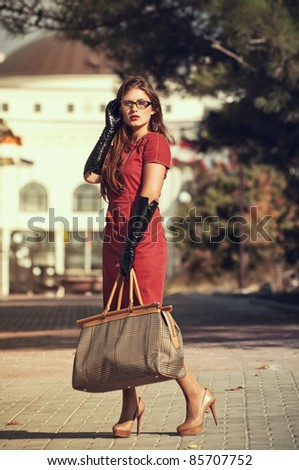 fashionable girl in red dress with bag crossing a city street