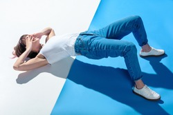 fashionable girl lying on floor, covering eyes with hands and doing hips raise