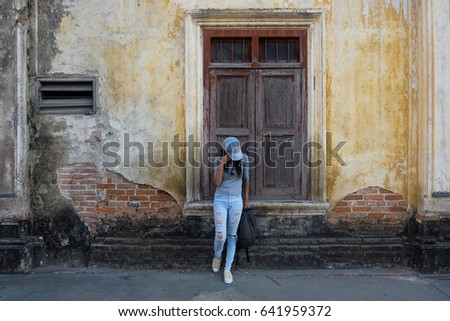 fashionable girl stands near the brick vintage wall