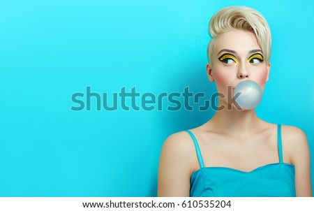 Stock Photo Fashionable girl with a stylish haircut inflates a chewing gum. The girl in the studio on a blue background. The girl's face with bright makeup and yellow with black shadows on the eyes.