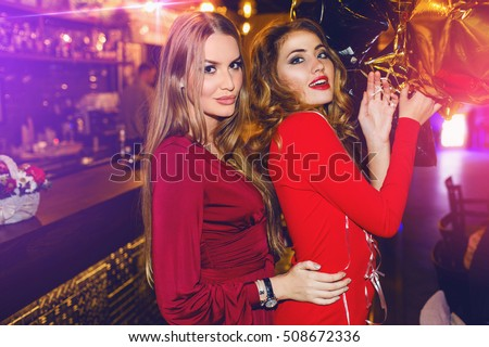 Fashionable girls, best friends posing in restaurant or  night club in stylish  sensual red dress with party balloons.  Drink cocktails, dancing. Bright make up. Wavy blonde hairstyle.  #508672336
