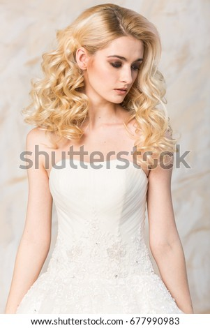 fashionable gown, beautiful blonde model, bride hairstyle and makeup concept - young pretty lady in white wedding festive dress, standing indoors on light background, romantic slender woman posing