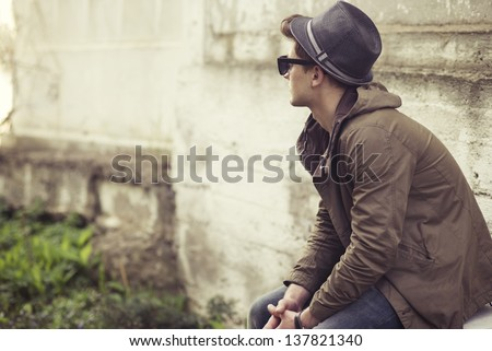 Fashionable guy sitting on a background of an old wall