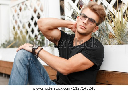 Fashionable handsome young man in glasses with a hairdo in a black T-shirt and jeans on the beach