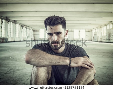 Fashionable Handsome Young Man Posing, Sitting on the Ground Inside an Empty Building While Looking at the Camera #1128751136