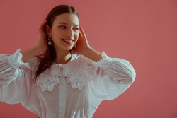 Fashionable  happy smiling brunette girl wearing trendy white vintage cotton blouse with lace collar, stylish pearl earrings posing on pink background. Copy, empty space for text