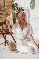 Fashionable happy smiling woman wearing white crochet jumpsuit, holding straw hat, with wicker bag, posing in stylish boho interior. Summer fashion conception