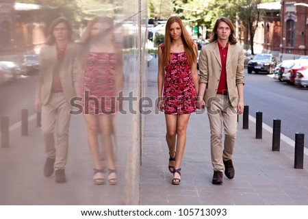 Fashionable happy young couple of a handsome man with long hair and attractive woman walking on the street holding hands