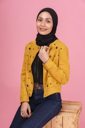 Fashionable hipster girl in dark blue jeans, long sleeves yellow leather jacket with hijab and sneakers isolated on pink background. Stylish Muslim hijab fashion lifestyle portraiture concept.