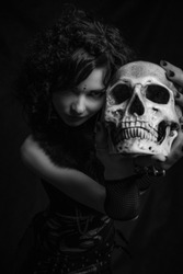 Fashionable kawaii witch with skull posing over dark background. Focus on girl's face not skull.